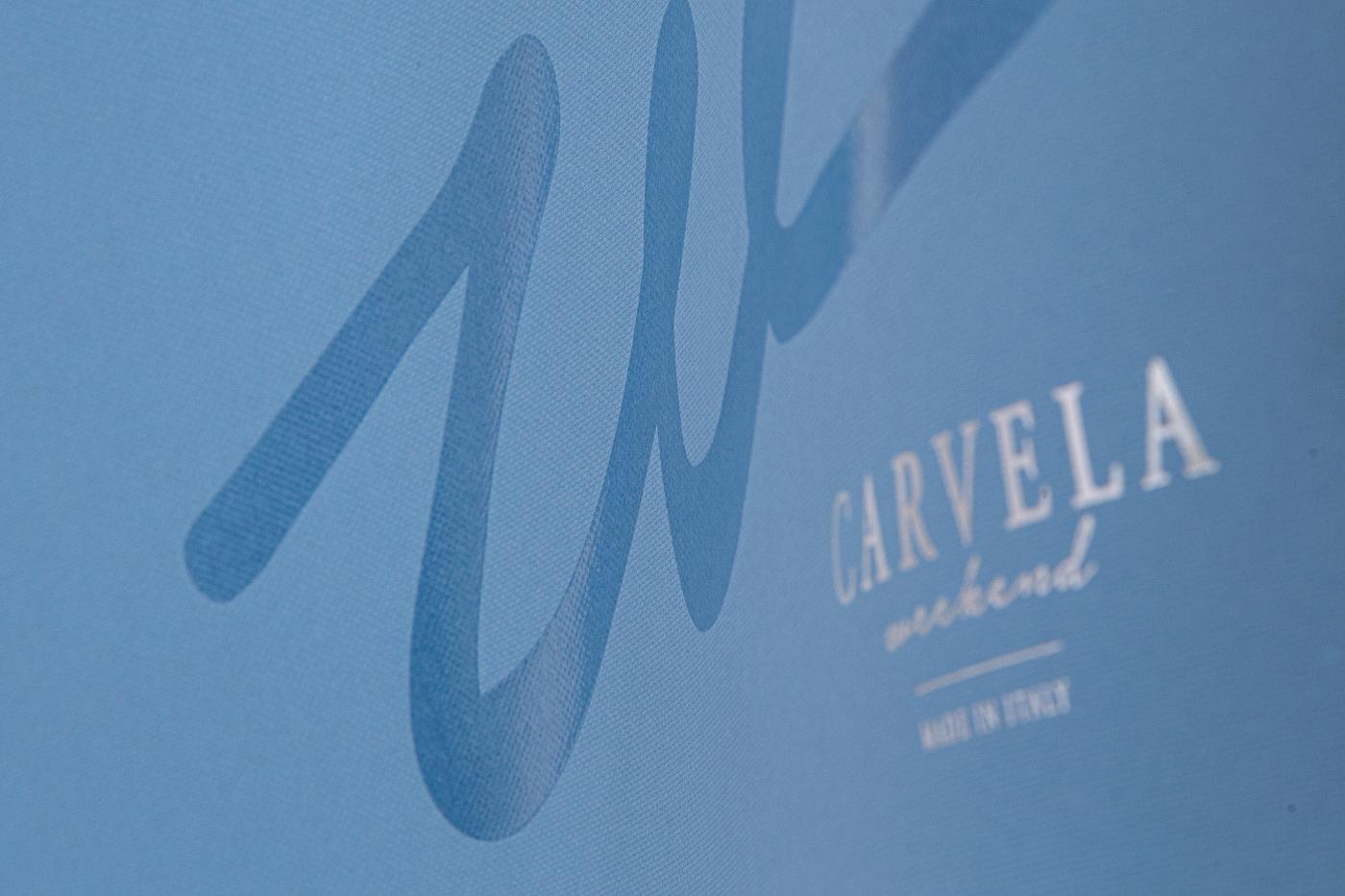 Carta colorata in pasta goffrata con una texture effetto tessuto e verniciatura serigrafica trasparente lucida